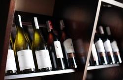 Wine bottles on a wooden shelf. Wine cellar background.