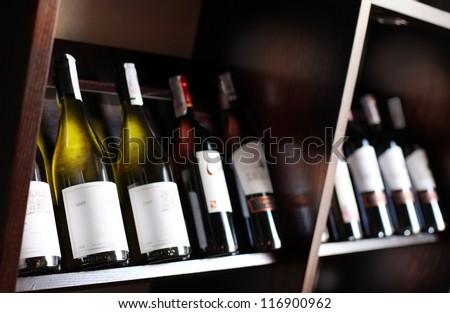 Wine bottles on a wooden shelf. Wine cellar background. #116900962