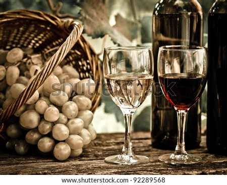 Wine bottles, two glasses and bunch of grapes in basket against vineyard in spring. Vintage look