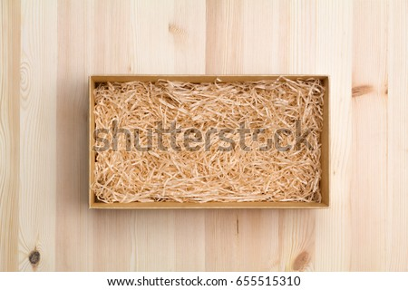 Wine box with decorative straw on wooden table, top view Stock photo ©