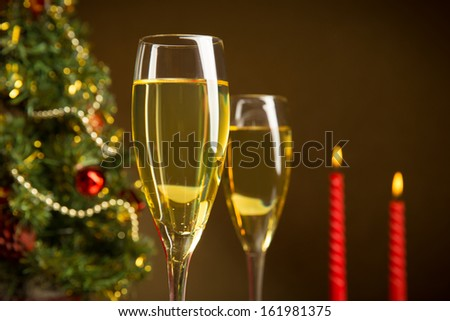 Wine by the glass and a candle with a Christmas tree #161981375