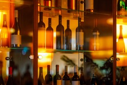 Wine cabinet with glass shelves and door and reflections. red and white wines