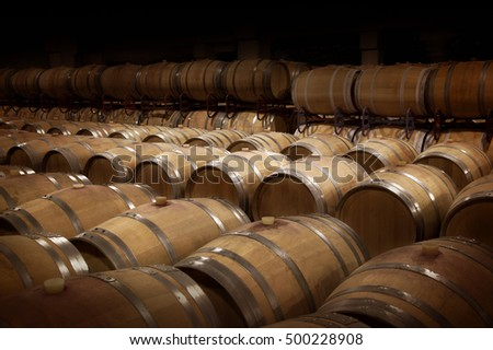 Wine cellar in warm ambiance. Rows of wooden wine barrels at a winery. #500228908