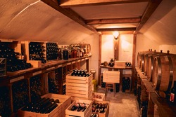 Wine cellar with bottles of alcoholic drink in wooden crates and barrels on wooden stands