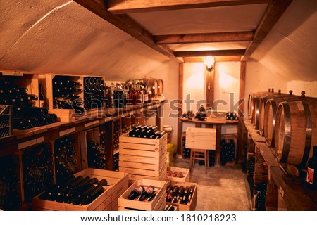 Wine cellar with bottles of alcoholic drink in wooden crates and barrels on wooden stands Foto stock ©