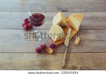 Wine, cheese and grapes on wooden table