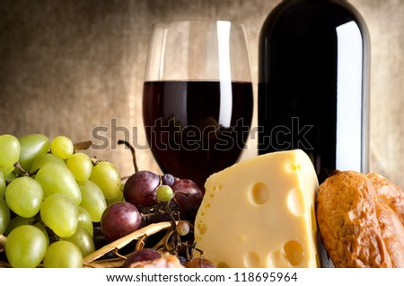 Wine, cheese, grapes and sausage on an old canvas