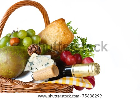 Wine, ciabatta, cheese, herbs, grapes and pear in a wicker basket for picnic.