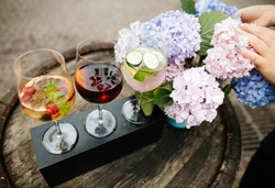 wine cocktails with macaroons and flowers on wooden barrel