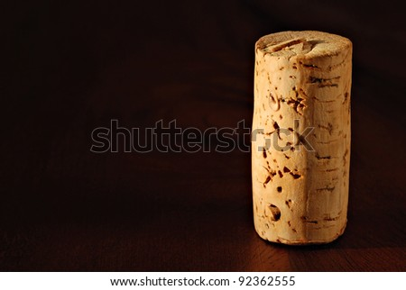 Wine cork with droplets of wine on wood background.  Macro with shallow dof.