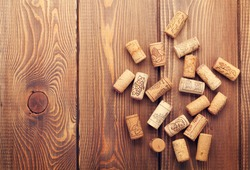 Wine corks over rustic wooden table background. Top view with copy space