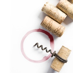 Wine corks, small corkscrew and round, red wine stain on white table cloth