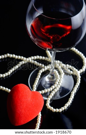 Wine glass and a red heart with pearls against black background