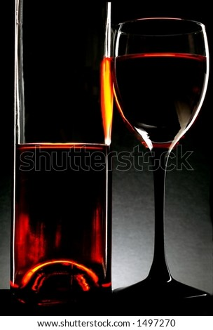 Wine glass and bottle against black background.