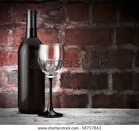 Wine glass and bottle on brick background with red hues copy space
