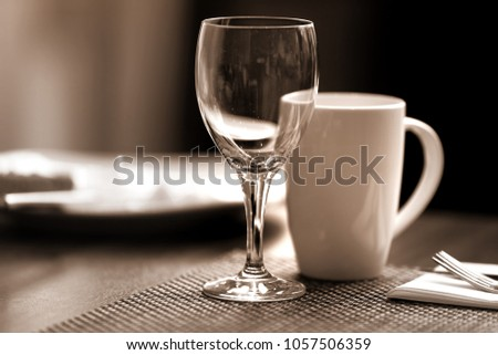 Wine glass and coffee cup on breakfast table #1057506359