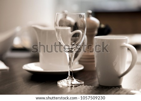 Wine glass and coffee cups on breakfast table #1057509230