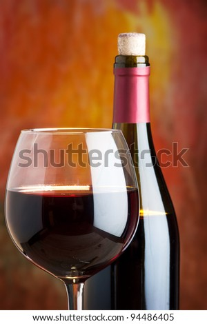 Wine, glass and the bottle on a colored background - stock photo