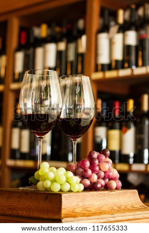 Wine glass, grape and bottles on the background.