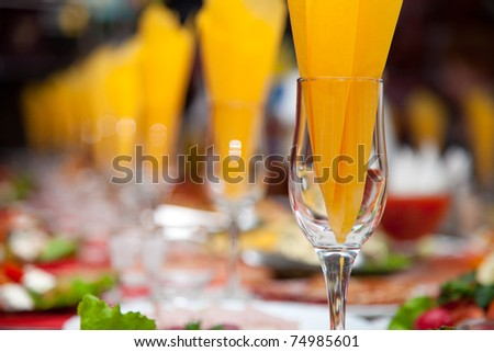 Wine glass with a napkin in the Inside on the background of the banquet table