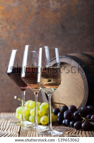 Wine glass with grapes and barrel. Red, white and rose