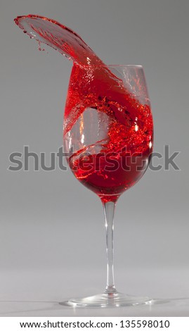 Wine glass with red liquid spill over grey background