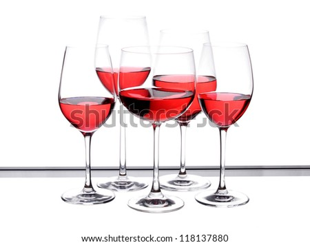 Wine glass with red wine in glass on the table, the five-piece with a black border.