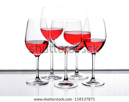 Wine glass with red wine in glass with four pieces wine glass empty one on the table with a black border.