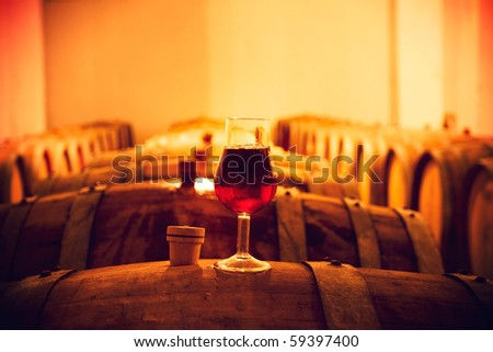 Wine glass with red wine on a cask in cellar