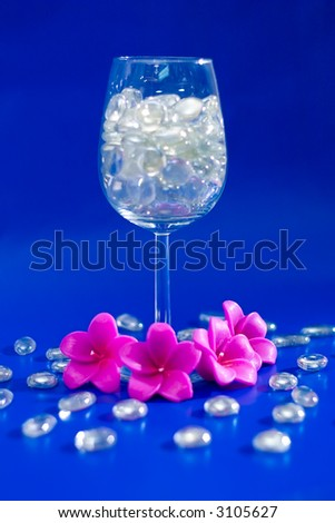 Wine glass with sparkling stones on a blue background