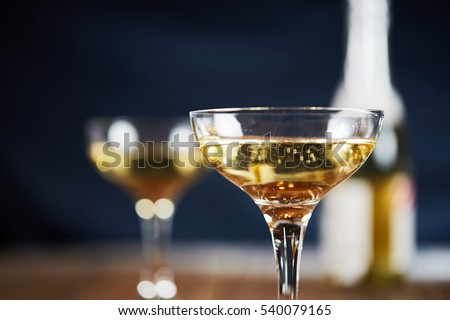 Wine glass with yellow sparkling wine in front of blue background