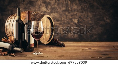 Wine glass, wooden barrel and collection of excellent red wine bottles in the cellar: traditional winemaking and wine tasting concept Foto stock ©