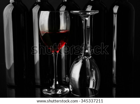 Wine glasses against bottles in a row on black background, close up #345337211