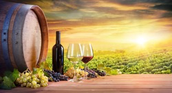 Wine Glasses And Bottle With Barrel In Vineyard At Sunset