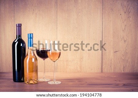 Wine glasses and bottles front wooden background