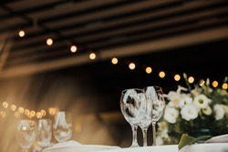 Wine glasses and champagne flutes on table. Wedding decor. Table setting in a restaurant. Empty wine glasses, plates on the tablecloth. Elegant restaurant interior.