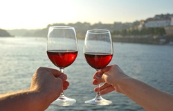 Wine glasses in the hands against Douro river in Porto, Portugal