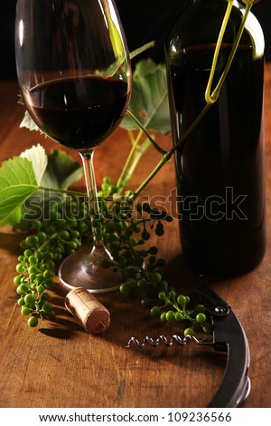 Wine goblet, bottle and cork on the wooden surface