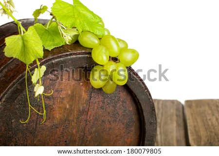 Wine grape and barrel with fresh grapevine border on