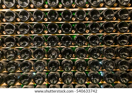 Wine in bottles storing in racks at warehouse of winery #540633742