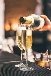 wine or champagne pouring in wine glass. concept for drink and beverage.Blur background