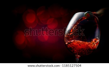 Wine pouring into wineglass on dark red background #1185127504