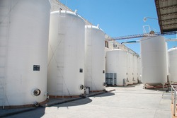 Wine processing and storage silos in winery. White cylindrical tanks with wine in a business in Salta, Argentina. Industrial barrels outside with blue sky.