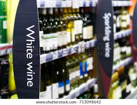 Wine shelf aisle in supermarket with White Wine ad on display in foreground