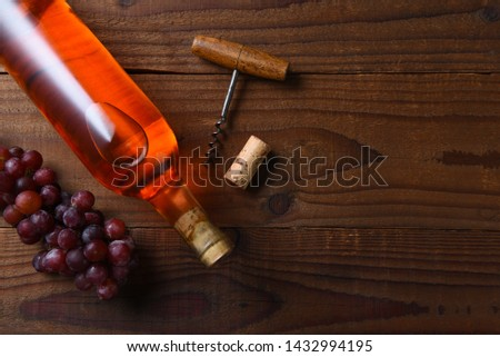 Wine Still Life: A blush wine bottle on a dark wood table with grapes and corkscrew, and copy space, shot from directly above. #1432994195