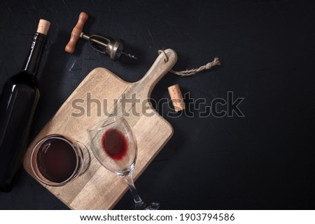 Wine tasting. A cork, a vintage corkscrew, a bottle, and two glasses, shot from above on a black background with a place for text Сток-фото ©