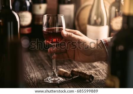 Wine tasting experience in the rustic cellar and wine bar: sommelier holding a glass of delicious red wine and excellent wine bottles collection on the background #685599889