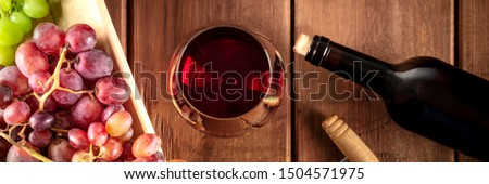 Wine Tasting Panorama. A red wine glass with a bottle, grapes, and a vintage corkscew, shot from the top on a dark rustic wooden background Сток-фото ©