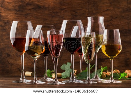 Wine tasting, still and sparkling wines. Red, white wine, rose and champagne шт assortment in wine glasses on vintage wooden table background