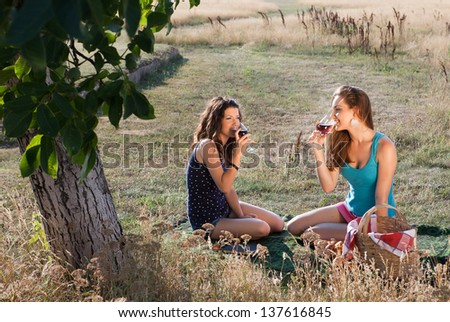 Wine tasting young women during a picnic in golden evening light
